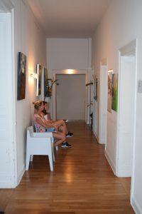 Flur mit drei weißen Stühlen und mehreren Türen. Auf zwei Stühlen sitzen Frauen und warten auf ihre Behandlung