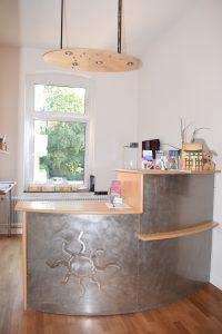 Eingangsbereich mit einer Theke aus Holz und Metall. Die Metallfront zeigt ein Sonnensymbol
