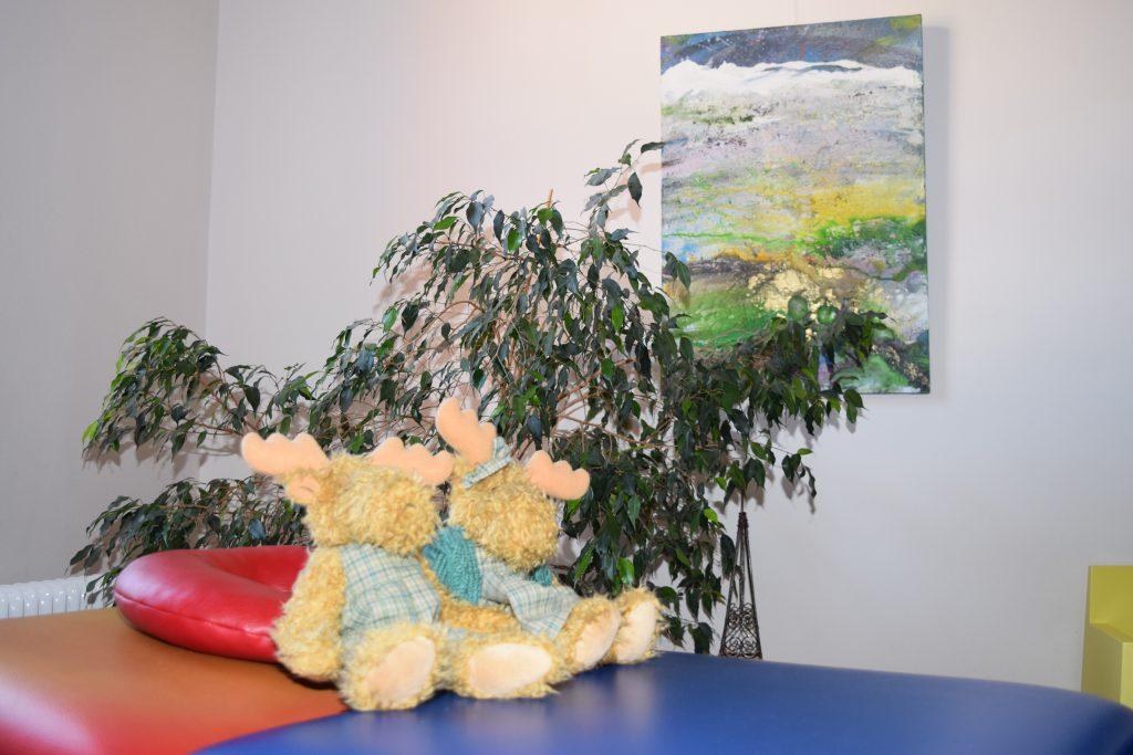 Zwei Stofftier-Elche auf einer rot-blauen Behandlungs-Liege für die Therapie