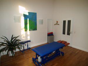 Behandlungsraum mit rot-blauer Liege für die Therapie