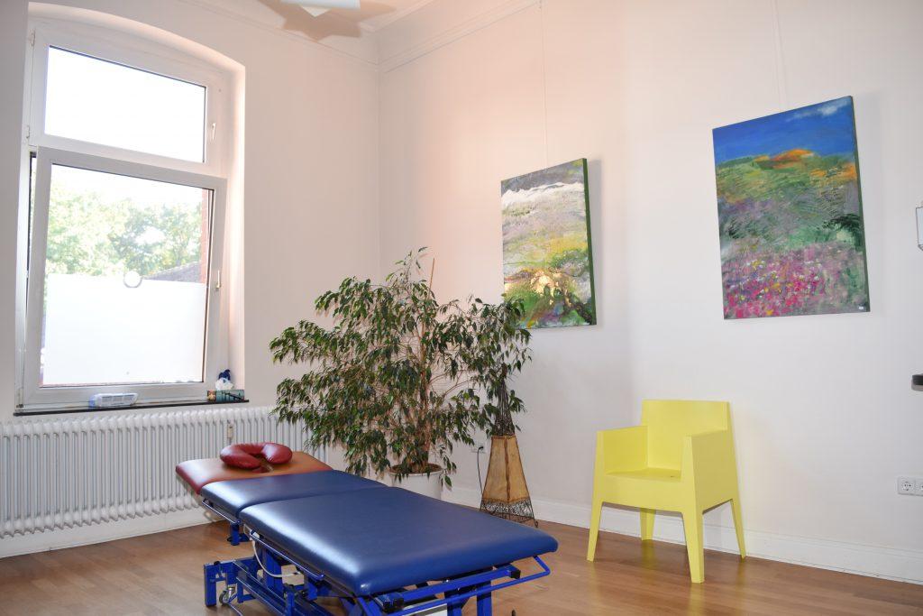 Raum mit blauerLiege für Massagen und andere Anwendungen, einem gelbem Stuhl und zwei Bildern an der Wand