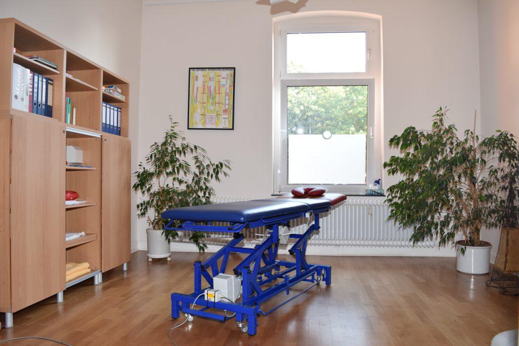 Raum mit blauer Liege, zwei großen Topfpflanzen und einem Aktenschrank