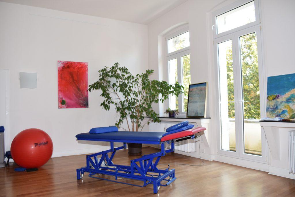 großer Raum mit riesigen Fenstern, einer Massageliege und einem roten Sitzball