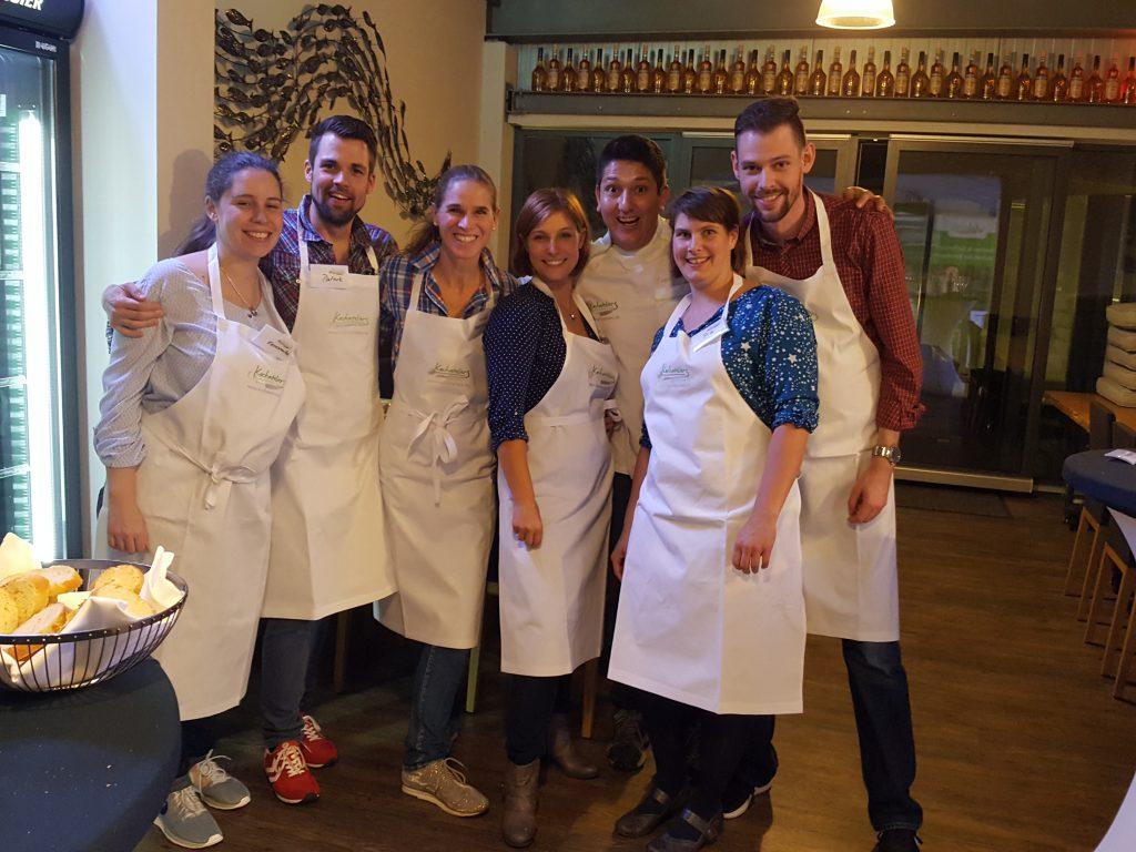 4 Frauen und 3 Männer lachend in Kochschürzen